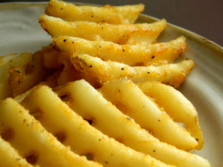 two waffle fries on plate with seasoning  Stockfoto