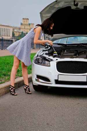 Cute brunette with red lips on high heels is posing with luxury white car  photo