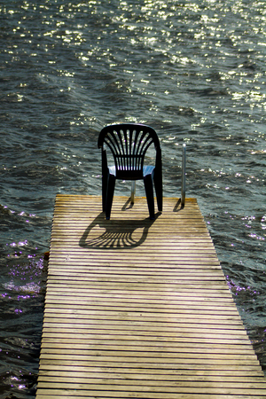 One vacant place available, empty chair by a lake Stock Photo