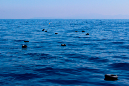 lifevest: Inner tubes of car tires and life vests floating in the Mediterranean sea, used by a boat of refugees for flotation