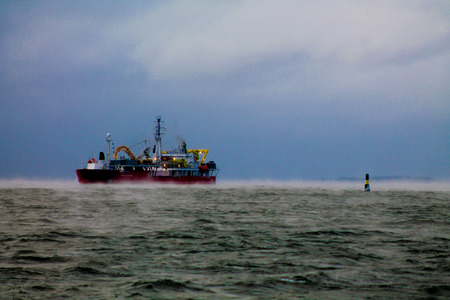 A cable ship and a navigational buoy in a hazy sea