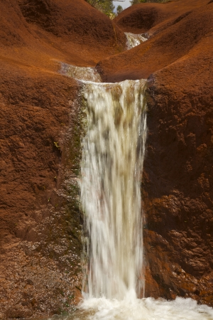 Water Rushing over Red Rocks  Waimea Canyon Kauai Hawaii Stock Photo
