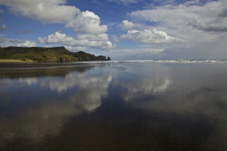 Sky reflection at Bethells beach in New Zealand. Auckland.  Stock Photo
