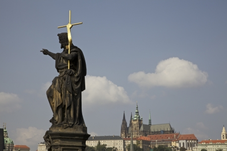 Statue on the famous Charles Bridge in Prague  The Castle is visible in the background  photo