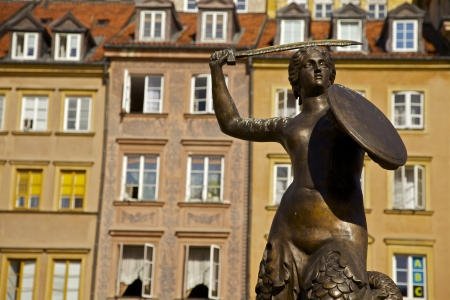 The mermaid statue in the old town square of Warsaw  Colorful housing sets the background