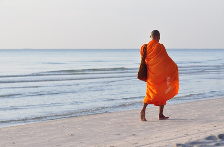 monk is walking on Hua Hin beach,Thailand