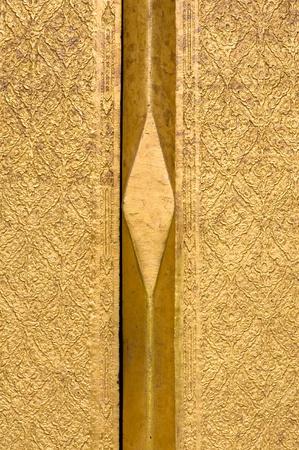 gold teakwood  door in a Thai temple in Thailand