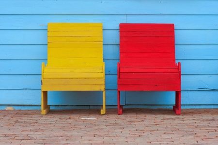 antique chair: red and yellow chairs on ancient red brick Stock Photo