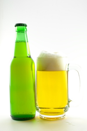bottle and glass of beer on white background photo