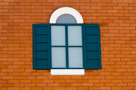 dark green vintage window on orange brick wall photo