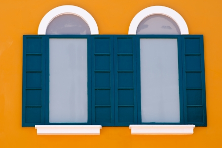 dark green vintage window on orange wall photo