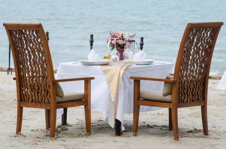 Outdoor restaurant tables, dinner setting on the beach photo