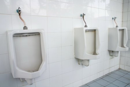 urinals on a marble tiled wall in a men photo