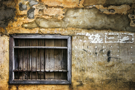 An old window in a facade of abandoned house Stock Photo