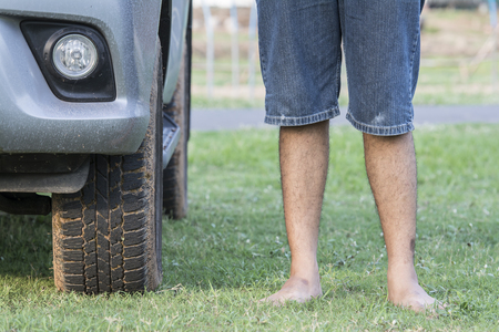 forklifts: Man standing barefoot on the grass beside the car.
