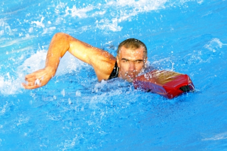 Athletic life guard swimmer training in a swimming pool photo