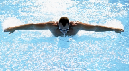 Athletic swimmer training hard in swimming pool photo