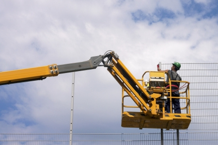 Hydraulic mobile construction platform elevated towards a blue sky with construction workers  Stock Photo