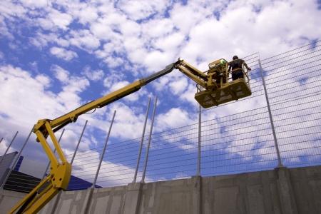 plataforma: Plataforma hidr�ulica m�vil de construcci�n elev� hacia un cielo azul con trabajadores de la construcci�n Foto de archivo
