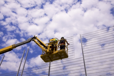 Hydraulic mobile construction platform elevated towards a blue sky with construction workers photo