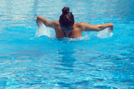 Nadador femenino bastante joven posando en la piscina photo