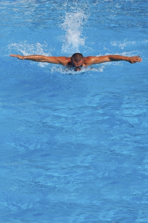 Athletic swimmer posing in a swimming pool photo