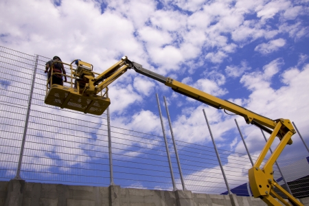 Hydraulic mobile construction platform elevated towards a blue sky with construction workers Stock Photo - 15382049