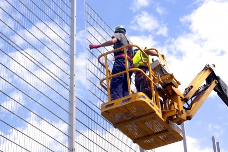 Hydraulic mobile construction platform elevated towards a blue sky with construction workers