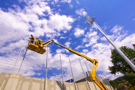 Hydraulic mobile construction platform elevated towards a blue sky with construction workers Stock Photo - 15646593