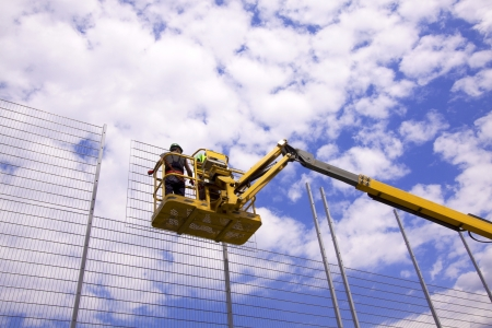 building site: Hydraulic mobile construction platform elevated towards a blue sky with construction workers