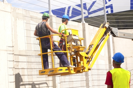 erector: Hydraulic mobile construction platform elevated towards a blue sky with construction workers