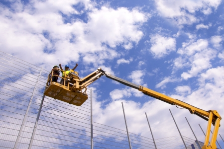 construction platform: Hydraulic mobile construction platform elevated towards a blue sky with construction workers