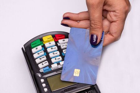 Female hand with credit card and bank terminal, Card machine or pos terminal with inserted credit card isolated on white background 스톡 콘텐츠