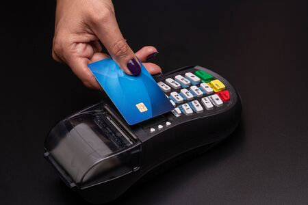 Female hand with credit card and bank terminal, Card machine or pos terminal with inserted credit card isolated on black background