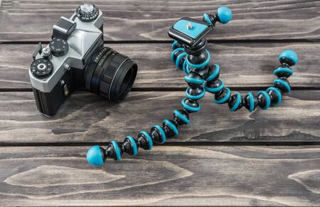Close up view of a flexible type tripod and vintage camera on wooden background