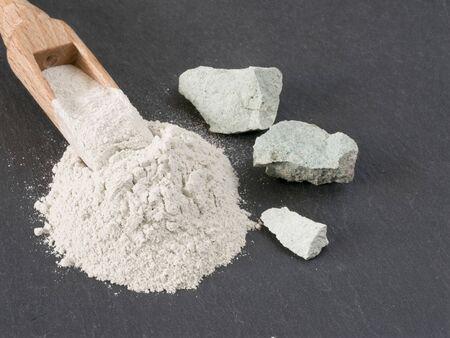 Zeolite natural raw stones and zeolite powder on black stone background.Macro shot