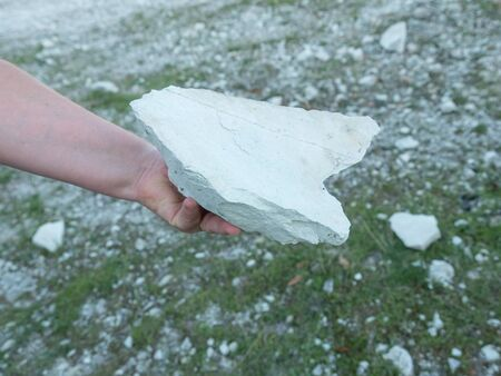 Female hand holding a  large natural raw zeolite rock