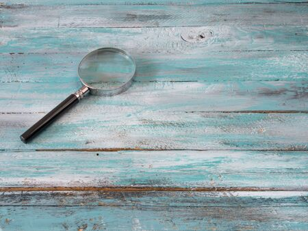 Magnify Glass on blue wooden background