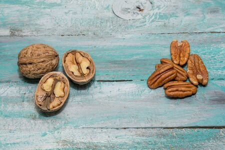 Tasty pecan  and walnuts  in wooden bowl on the old background.