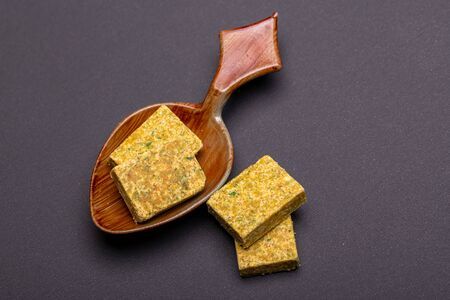 Vegetable bouillon stock or broth cube on wooden spoon