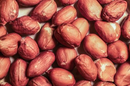 Peanuts, for background or textures, uncleaned in shell peanuts. Peeled peanut on well peanuts