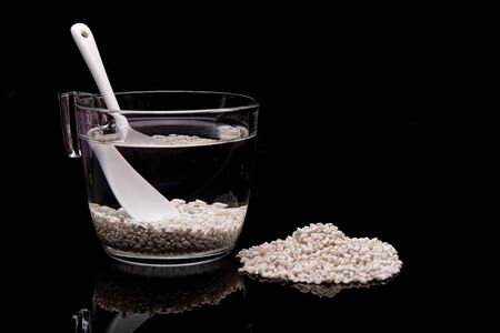 Zeolite pebbles in glass of water on black background