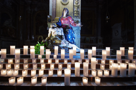 Rome  Italy - April 22 - 2015: Statue of Our Lady of sorrows (Mater Dolorosa) holding Jesus behind the candles at San Marcello al corso church. Front view