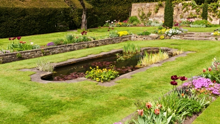 Scenic view of pond in flowery landscaped garden