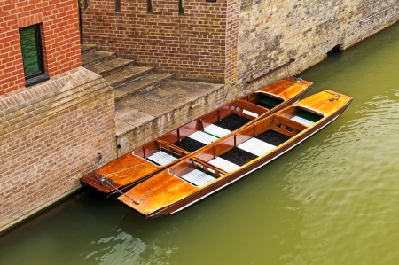 Two wooden punts or small boats next to brick building