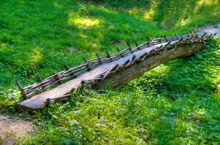 Small, old wood bridge crossing grassland