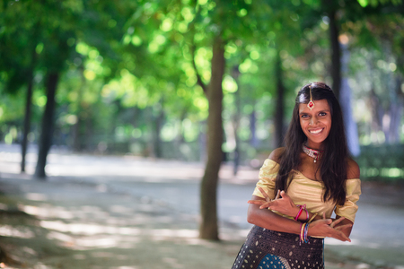 Young beautiful indian woman wearing traditional indian clothes, doing bollywood dance gestures with hands outdoors Stock Photo