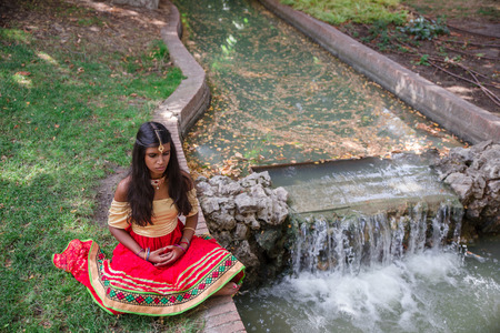 Young beautiful traditional indian woman practicing yoga in a peaceful nature environment, siddhasana pose Stock Photo