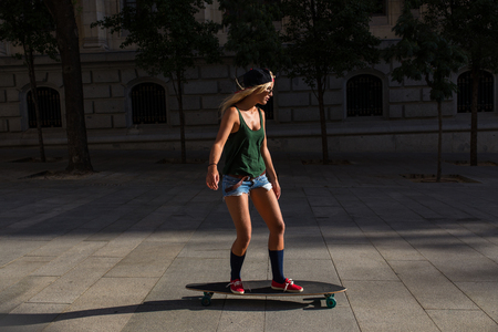 attractive young l woman who is wearing casual clothes, riding a skateboard