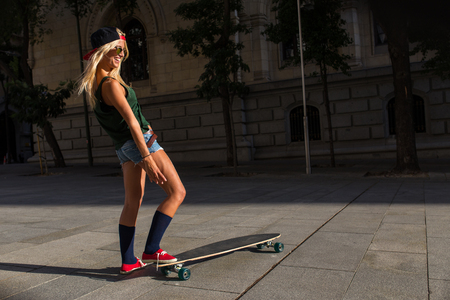 attractive young l woman who is wearing casual clothes, riding a skateboard Banco de Imagens